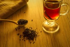 Brewing tea, spoon with tea leaves and cup of tea. Brewing tea wooden spoon with tea leaves and cup of tea still life Royalty Free Stock Photos