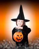 Brewing Up Something. A young witch is using her magic to brew something up Royalty Free Stock Photography