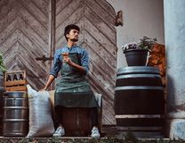 Brewmaster sitting on wooden barrel and holds a glass of craft beer relaxes after work. Brewmaster sitting on wooden barrel and holds a glass of craft beer royalty free stock photo
