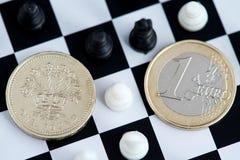 Brexit一英磅和欧元硬币在棋盘 图库摄影