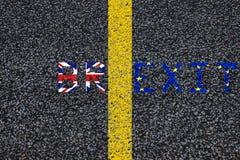 Brexit蓝色欧盟欧盟下垂和英国英国英国旗子,在柏油碎石地面,路标分离林的黄色油漆 免版税库存照片