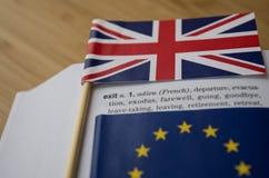 Brexit begrepp: Britten och EU-flaggor på en ordboksida som betonar ordet, går ut Arkivbilder