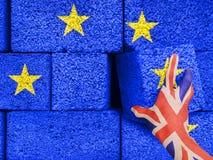Brexit begrepp - den Britannien handen tar tegelsten ut ur väggen av det gemensamma huset av den europeiska unionen royaltyfri bild