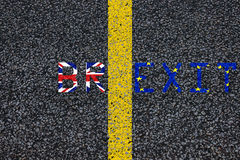 Brexit blue european union EU flag and uk great britain united kingdom flag, over tarmac, road marking yellow paint separating lin Royalty Free Stock Photo