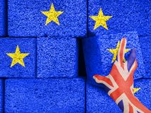 Brexit concept - Britain hand takes brick out of the wall of the common house of the European Union. royalty free stock image