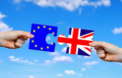 Brexit concept. Hands holding puzzle with flag of the UK and EU stock image