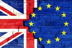 Brexit UK: concept for Brexit political crisis as cracked brick wall with UK and EU flags painted over the divided bricks. Brexit concept: European Union EU and stock images
