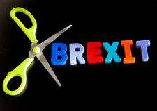 Brexit cuts. Text `brexit` in colorful uppercase letters surrounded with scissor blades ; concept of cuts caused by brexit Britain leaving European Union such as stock photos