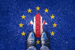 Brexit, flags of the United Kingdom and the European Union on asphalt road. With legs stock images