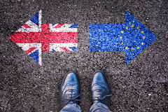 Brexit, flags of the United Kingdom and the European Union on asphalt road. With legs stock photography