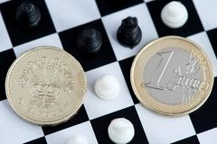 Brexit One British Pound and Euro coin on chess board. stock photography