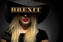 Brexit som är skriftlig på den svarta hatten Kvinna i svart stor hatt Royaltyfri Bild