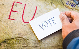 Brexit UK EU referendum concept with word UN and Eng and vote on hand on stone wall. Background stock photography