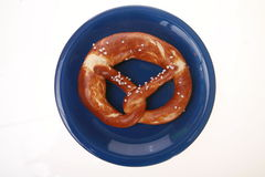 Brezel on a blue plate Stock Photography