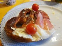 Brezel och rökte köttskivor, tomater Royaltyfria Foton