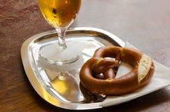 Brezel- und Bierglas auf einem Metallbehälter mit einer weißen Serviette Stockfotografie