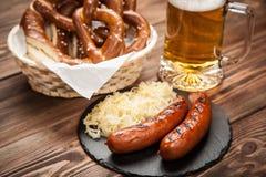 Brezeln, Bratwurst und Sauerkraut auf Holztisch stockfotos