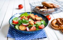 Brezensalat - παραδοσιακή γερμανική pretzel σαλάτα με το σπανάκι, τις ντομάτες, το ραδίκι και το αγγούρι Στοκ Εικόνες