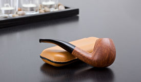 Briar and cigars case. A briar pipe on sofa with a case for cigars Royalty Free Stock Photography