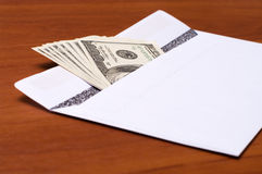 Bribe. Dollar bills in a white envelope on the office desk Royalty Free Stock Photography
