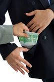 Bribe. Hands putting bribe into a pocket. The receiver kindly accepts the donation Royalty Free Stock Photo