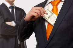 Bribe, concept for corruption. Businessman putting money in suit jacket pocket, concept for corruption, bribing Royalty Free Stock Photo