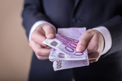 Bribe and corruption with euro banknotes. Man in Men`s Suits.Bribe and corruption with euro banknotes stock image