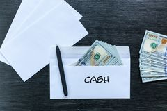 Bribe in an envelope. Cash. White envelopes with money lie on a black wooden table. Bribe in an envelope. Cash stock photo