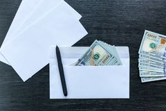 Bribe in an envelope. White envelopes with money lie on a black wooden table. Bribe in an envelope royalty free stock image