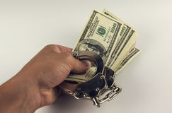 Bribe, hand giving dollars with handcuffs Royalty Free Stock Photography