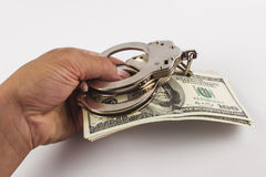 Bribe, hand giving dollars with handcuffs Stock Photo