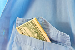 Bribe in his pocket. The money is in the pocket of a blue shirt Royalty Free Stock Photography