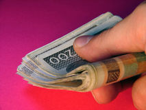 Bribe money. Pile of money in a hand. Red background Stock Image