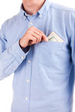 Bribe in pocket of shirt with hand isolated. On white Royalty Free Stock Images