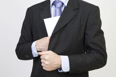 Bribery. Businessman puts a white envelope in his pocket Royalty Free Stock Photos