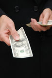 Bribery. Female hands holding hundred dollars bills out if front of her while wearing a black coat Stock Photo