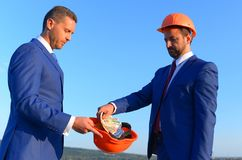 Bribery and business bargain concept. Architects with serious faces. In formal wear and helmets share budget. Builder puts money into coworkers orange helmet stock photo