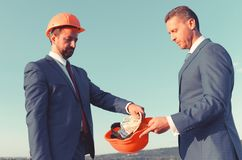 Bribery and business bargain concept. Architects with serious faces. In formal wear and helmets share budget. Builder puts money into coworkers orange helmet royalty free stock photography