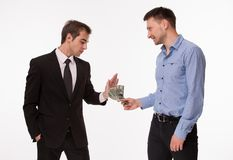 Bribery. Businessman in dark-coloured business suit rejecting money from men in blue-coloured shirt. Two men posing on white Stock Photography