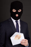 Bribery concept - man in business suit and mask holding envelope Royalty Free Stock Image