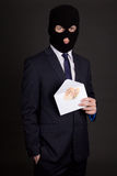 Bribery concept - man in business suit and mask holding envelope Stock Image