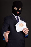 Bribery concept - man in suit and mask with money in envelope re Stock Photography