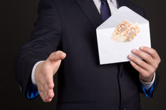 Bribery concept - man in suit with money in envelope ready to ha Royalty Free Stock Photos