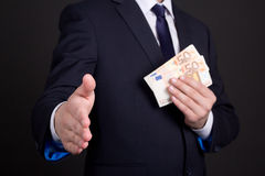 Bribery concept - man in suit with money ready to handshake Royalty Free Stock Photos