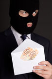 Bribery concept - masked man in suit holding envelope with money Royalty Free Stock Photos