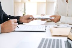 Bribery and corruption concept, bribe in the form of dollar bill. S, Businessman giving money in the envelope while making deal to agreement a real estate Stock Photography