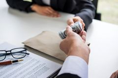 Bribery and corruption concept, bribe in the form of dollar bill. S, Businessman giving money while making deal to agreement a real estate contract and financial Royalty Free Stock Photography