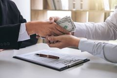 Bribery and corruption concept, bribe in the form of dollar bill. S, Businessman shaking hands and giving hides money while making deal to agreement a contract Royalty Free Stock Image