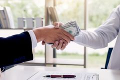 Bribery and corruption concept, bribe in the form of dollar bill. S, Businessman shaking hands and giving hides money while making deal to agreement a contract Royalty Free Stock Photo