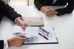 Bribery and corruption concept, bribe in the form of dollar bill. S, Businessman giving money in the envelope while making deal to agreement a real estate Royalty Free Stock Photography